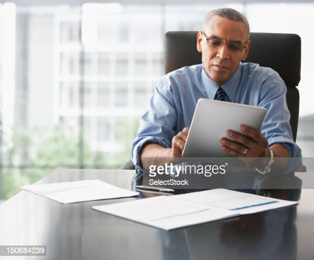 Businessman looking over electronic tablet : Stockfoto