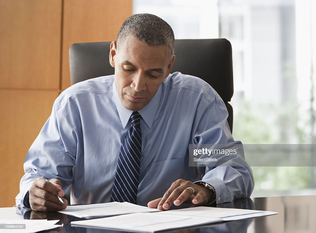 Businessman looking over reports : Stock Photo