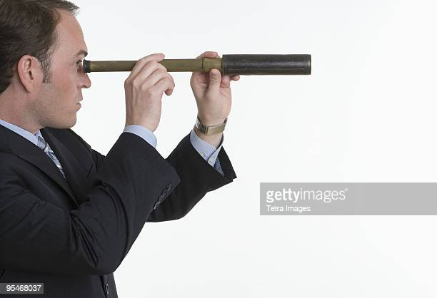 Businessman looking through a periscope