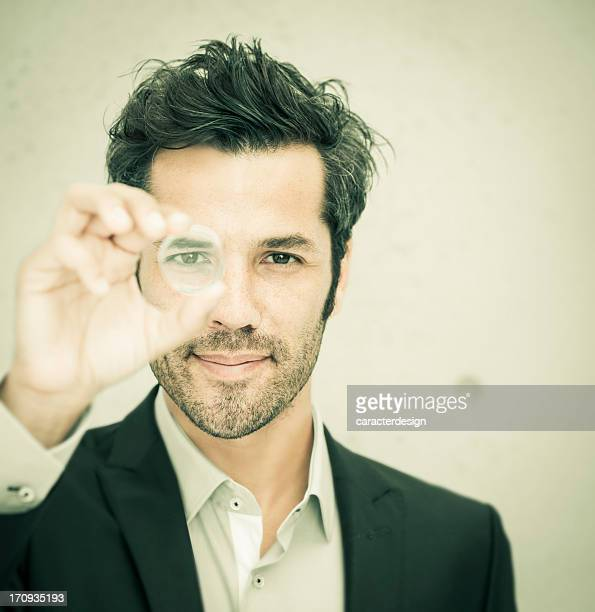 Businessman looking through a round lens
