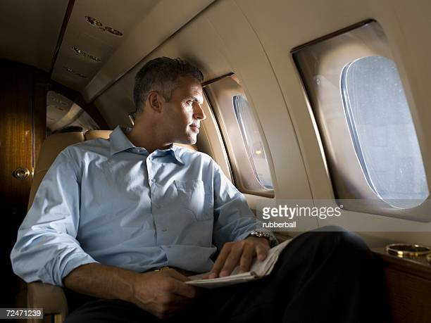 A businessman looking through an airplane window