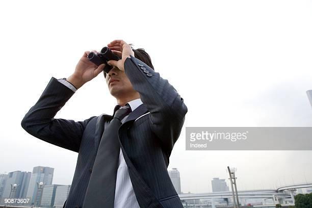 Businessman looking through binoculers