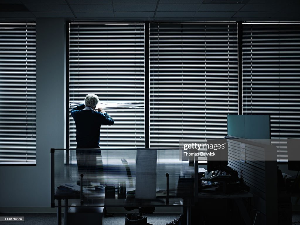 Businessman looking through closed blinds