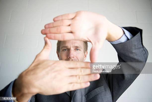 Uomo d'affari guarda attraverso telaio con le mani