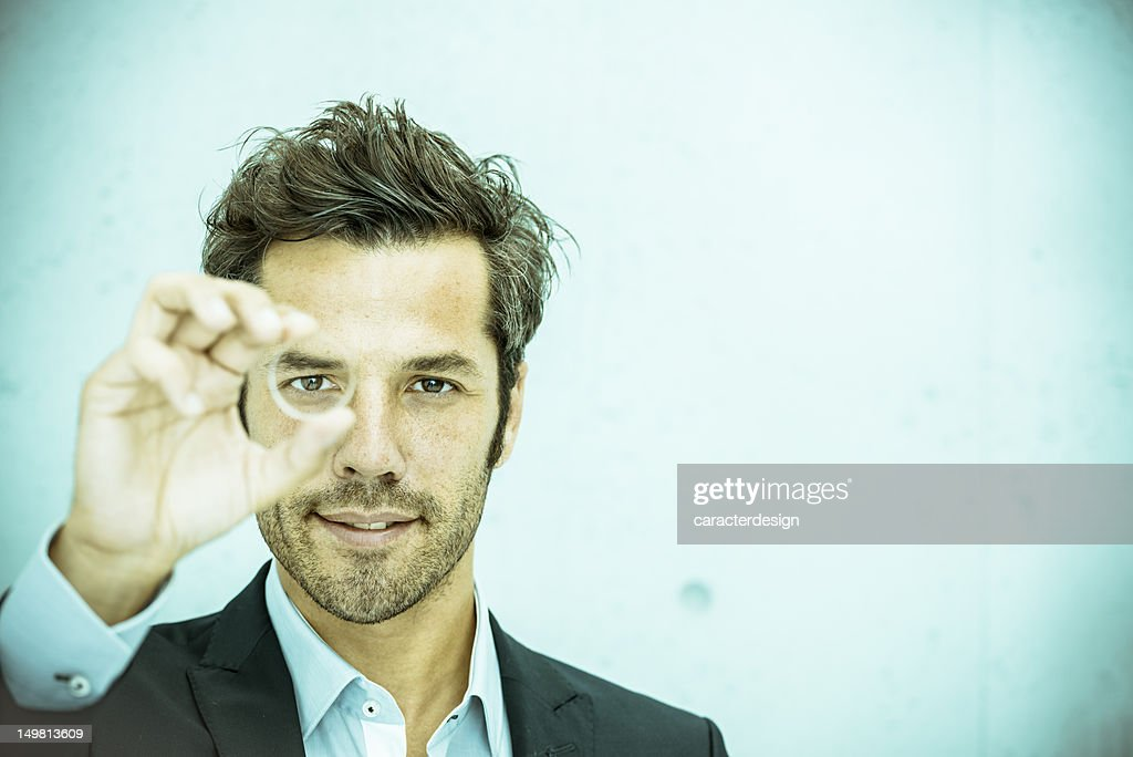 Businessman looking through lens : Stock Photo