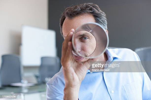 Businessman looking through metal cylinder in office