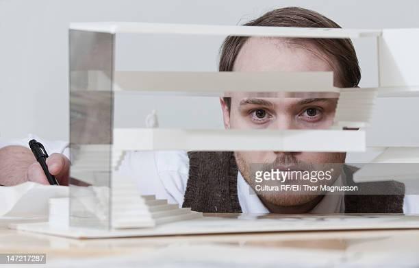 Businessman looking through model