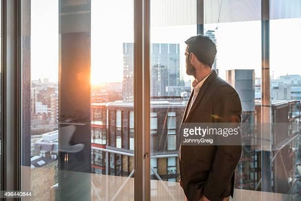 Hombre de negocios mirando a través de la ventana de la oficina en la luz del sol