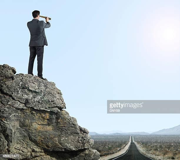 Empresário Olhando através do Telescópio pequeno no Deserto