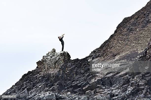 Businessman Looking Through Spyglass On Rugged Mountain