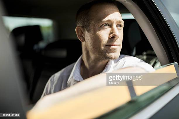 Businessman looking through taxi window