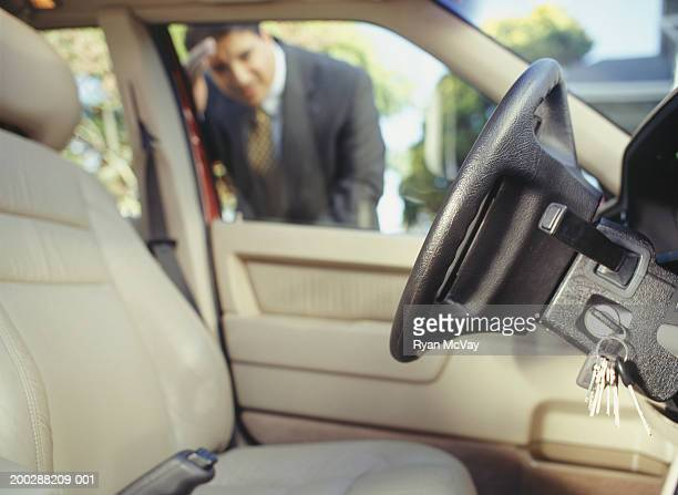 Businessman looking through window at keys locked in car