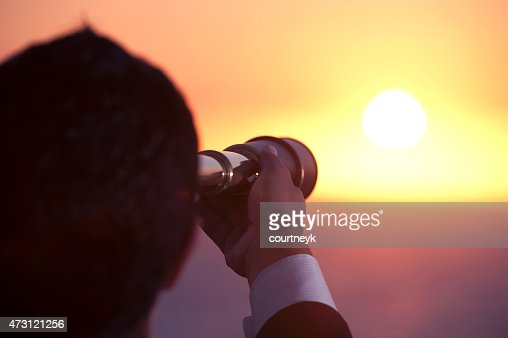 Businessman looking to the future with telescope at sunrise.