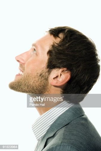 Businessman looking up and smiling, side view : Stock Photo