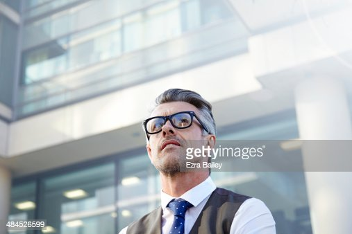 Businessman looking up at a sky scraper.