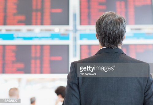 Businessman looking up at arrival departure board in airport