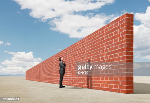 Businessman looking up at brick wall in middle of desert