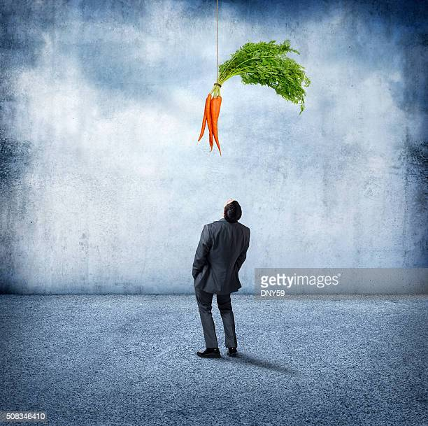 Businessman Looking Up At Carrots Dangling Above Him