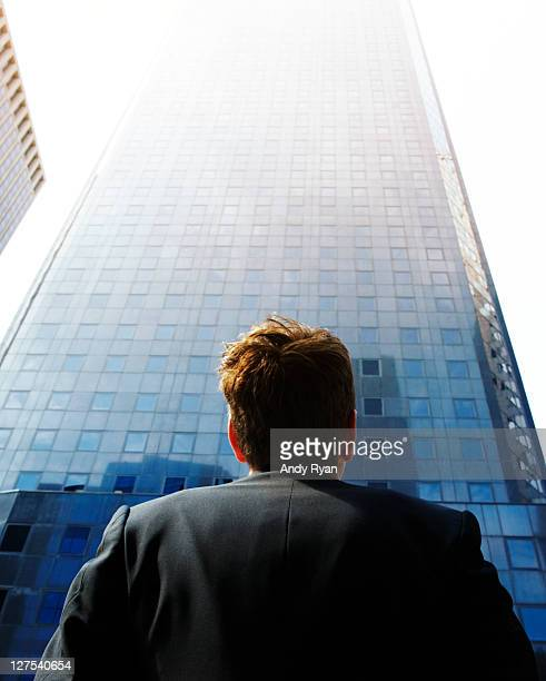 Businessman looking up at city skyscraper.