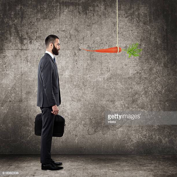 Businessman looking up at dangling carrot