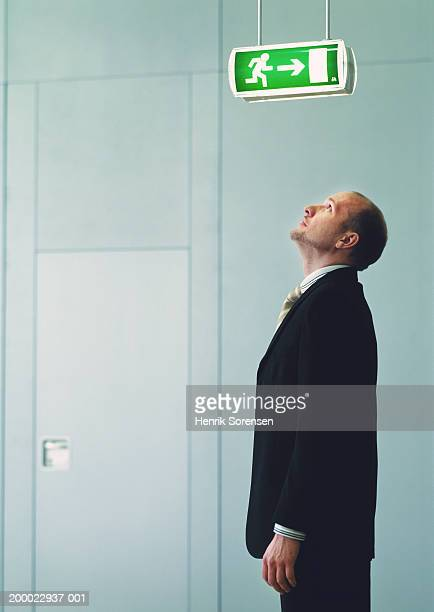 Businessman looking up at emergency exit sign