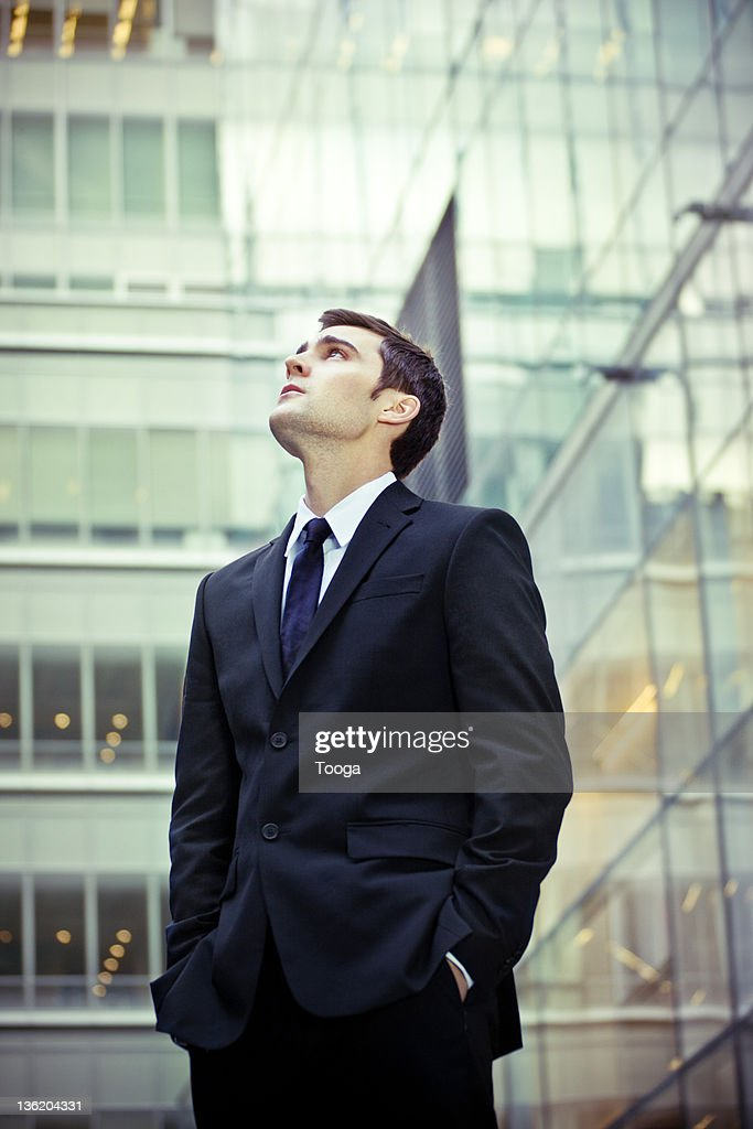 Businessman looking up at office building : Stock Photo