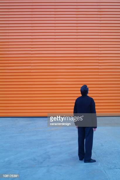 Businessman Looking Up at Orange Building Facade