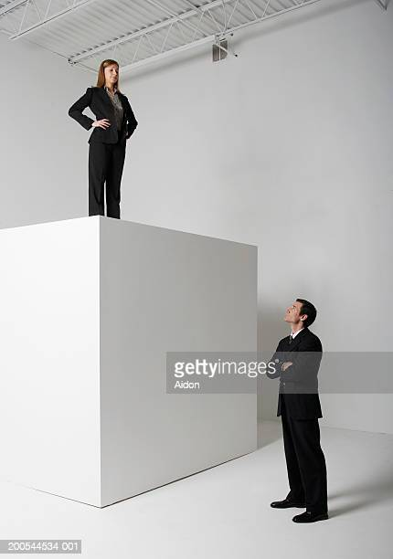 Businessman looking up at woman on top of cube, studio shot