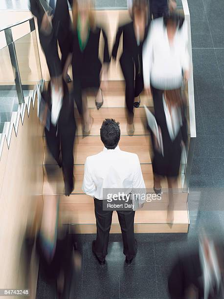 Businessman looking up busy office staircase