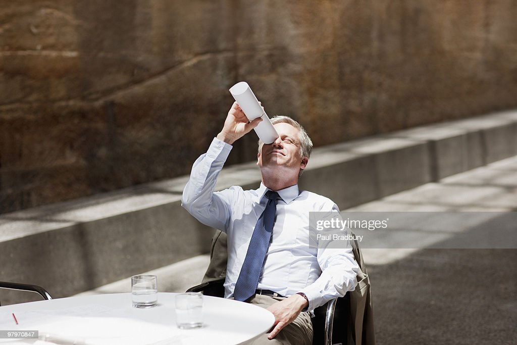 Businessman looking up through rolled up paperwork : Stock Photo