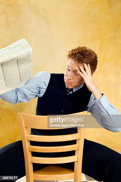 Businessman looking upset while reading a newspaper