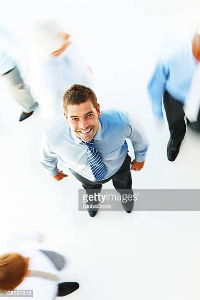 Businessman looking upward and with people walking around