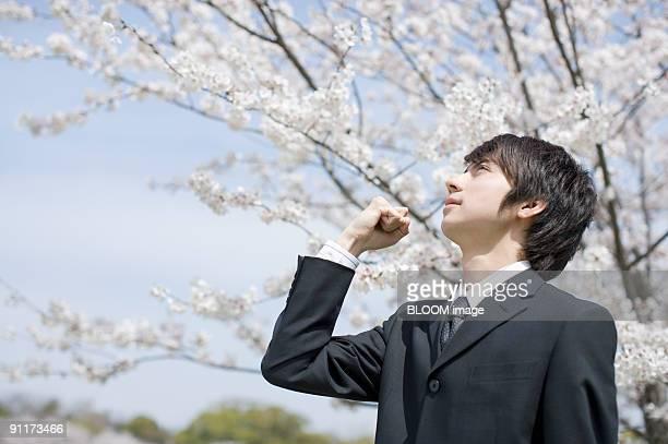 Businessman looking upward, clenching fist, side view