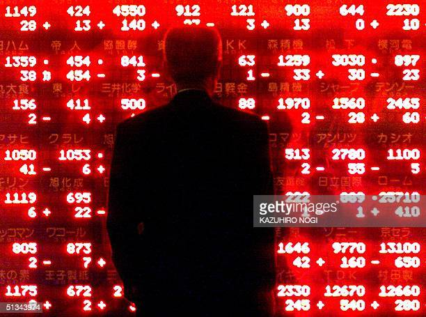 A businessman looks at an electronic stock share prices board in downtown Tokyo 19 October 2000 Shares fell 04 percent on selling of hitech issues as...