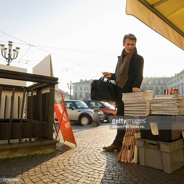 Businessman looks at magazines on stand, city