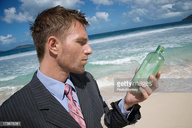 Uomo d'affari esamina messaggio in una bottiglia