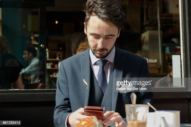 Businessman looks at mobile phone, sitting in coffee shop.
