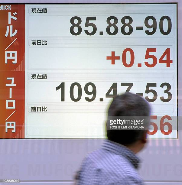 A businessman looks at the foreign currency rates including the yen against the US dollar on the electronic indicator in the window of a securities...