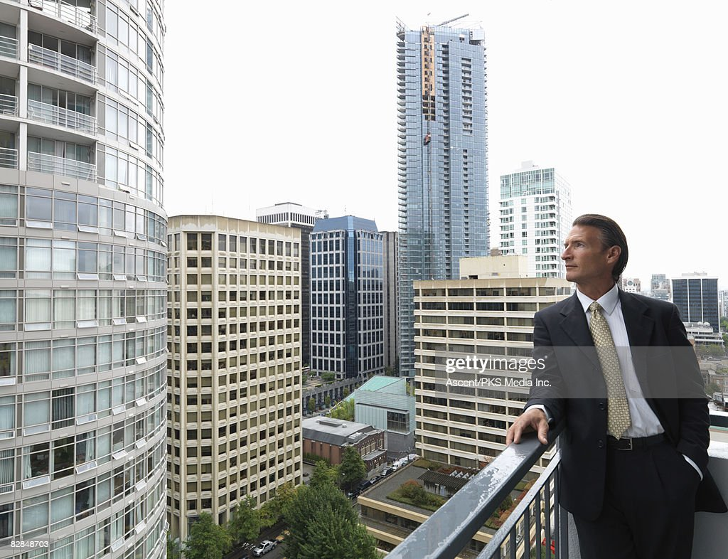 Businessman looks off deck of high rise in city : Stock Photo