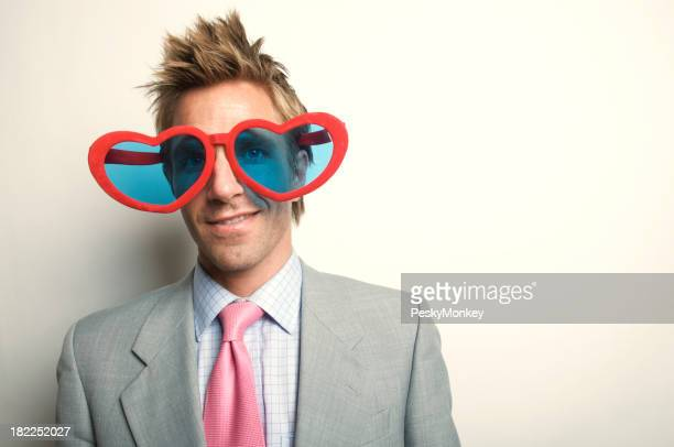 Businessman Looks through Heart Shaped Glasses