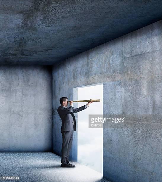Businessman Looks Through Spyglass From Inside Building