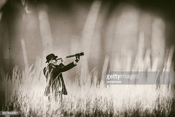 Businessman looks through spyglass on tall grass