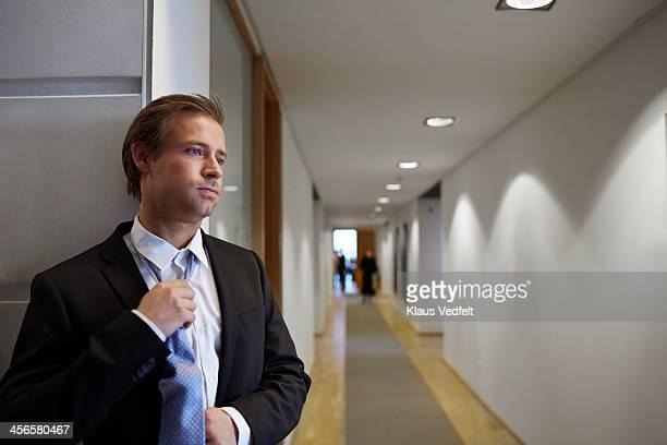 Businessman Loosening his tie, standing on aisle