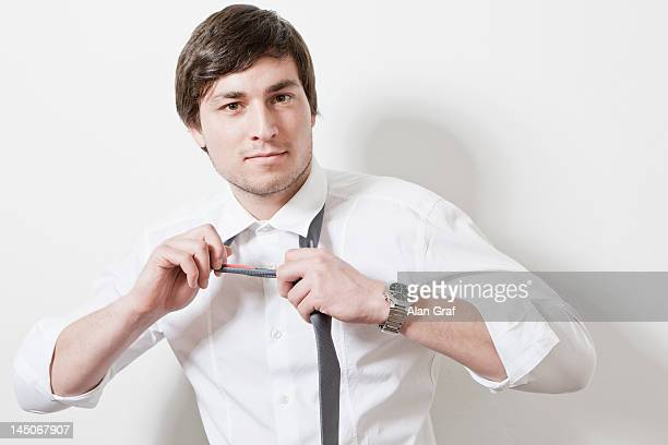 Businessman loosening tie in office