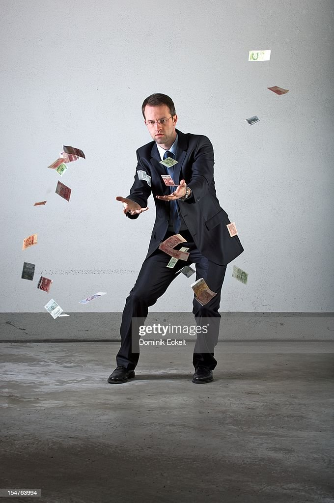 A businessman losing paper money : Bildbanksbilder