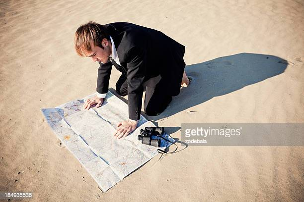 Businessman Lost in the Desert Looking at a Map