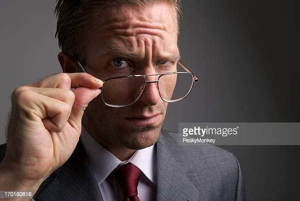 ビジネスマンが傾斜をメガネ、重大な表情