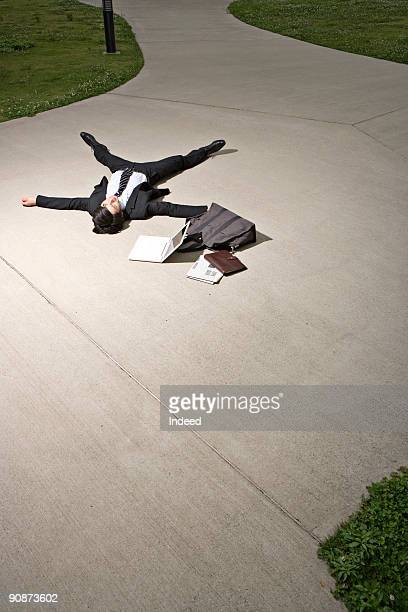 Businessman lying down on street