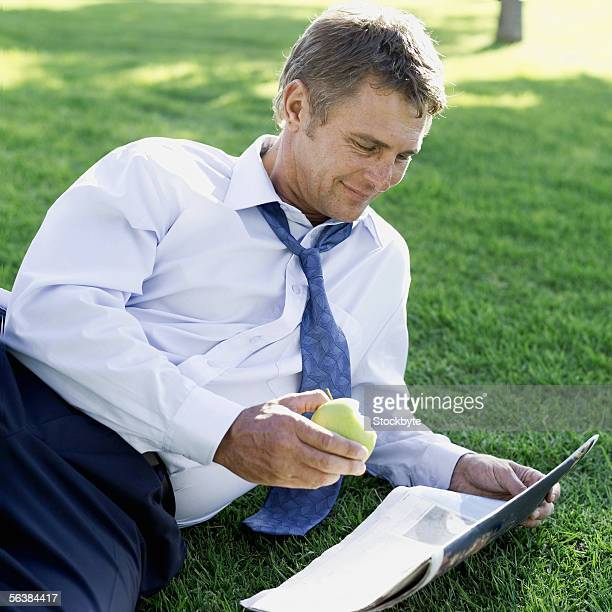 businessman lying in a park reading a newspaper