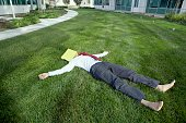 Businessman lying in the grass with a file folder over his face